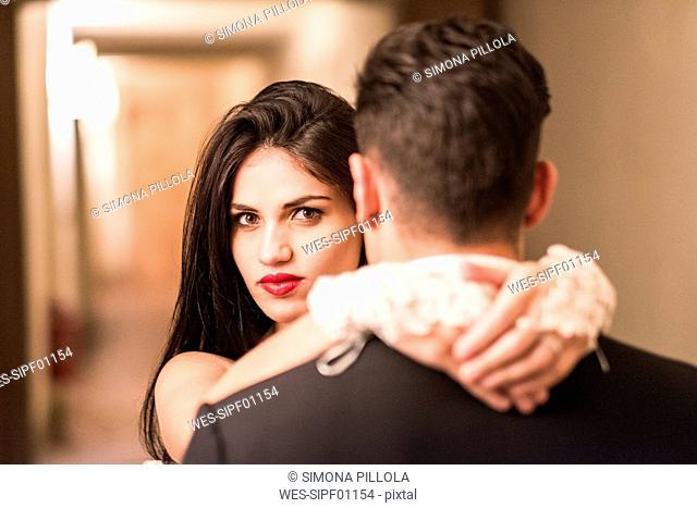 Portrait of bride embracing groom