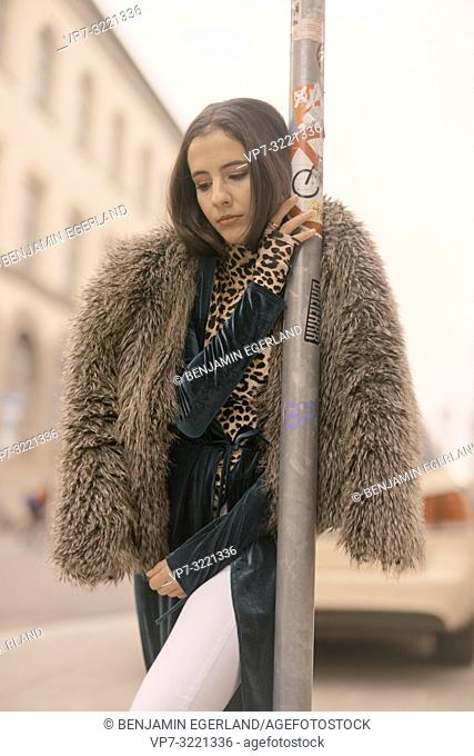 thoughtful woman leaning on lamppost at street in city, exhausted, tired, sleepy, Munich, Germany