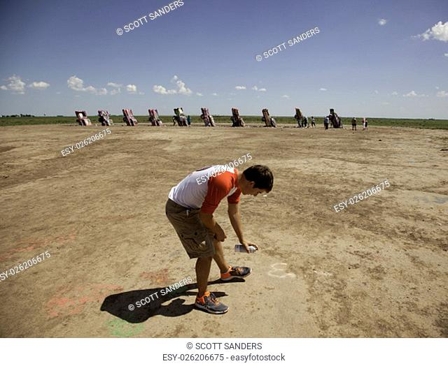 A teenage boy spray painting the ground at Cadillac Ranch in Amarillo, Texas on July 13, 2015