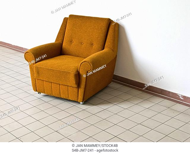 Empty armchair on tiled floor