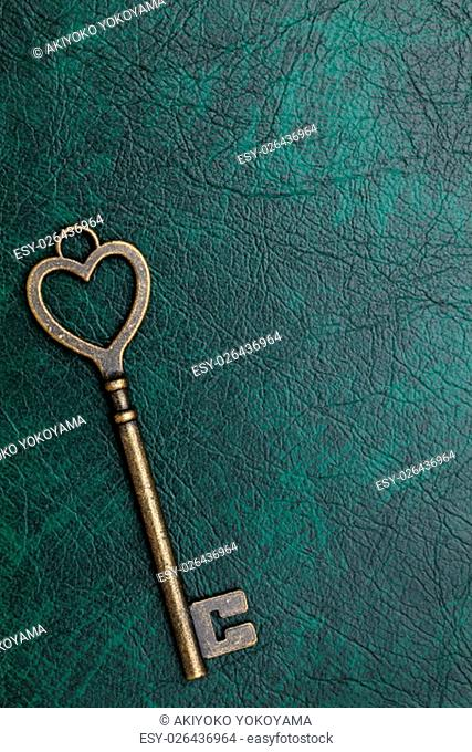 heart shaped vintage key on a leather background