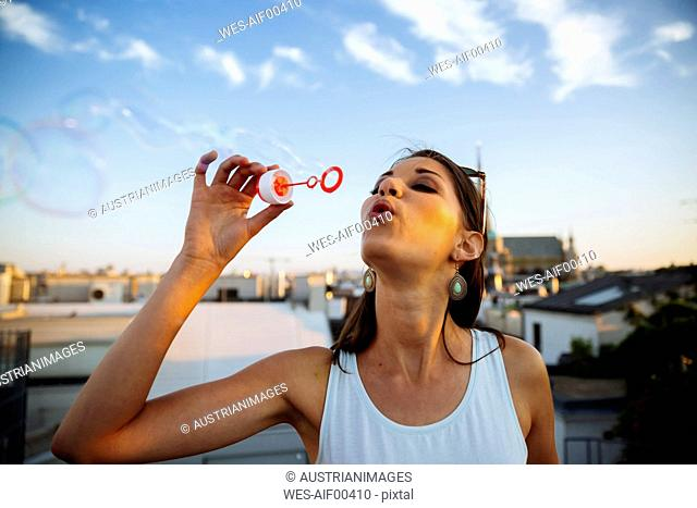 Austria, Vienna, young woman blowing soap bubbles on roof terrace
