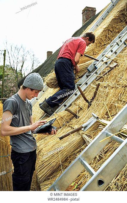 Two thatchers thatching a roof, one using a digital tablet the other standing on a ladder