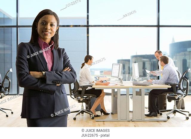 Smiling businesswoman standing with arms crossed and co-workers working in background