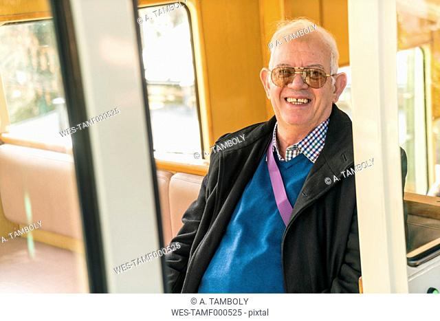 Germany, Dresden, smiling senior man sitting in cable railway