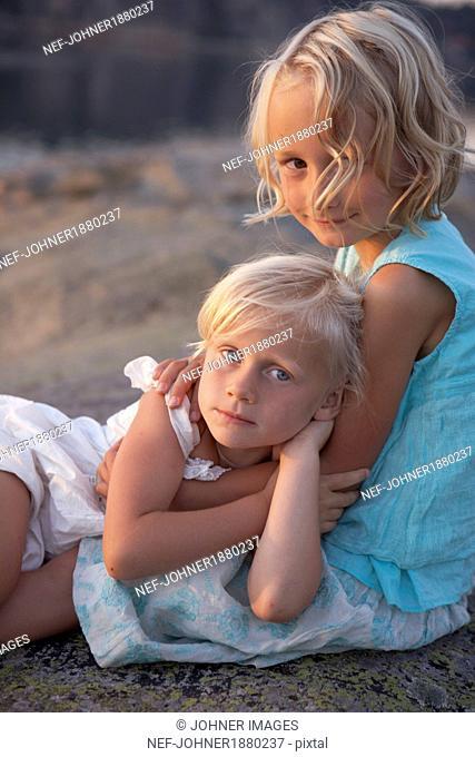Two girl hugging and looking at camera
