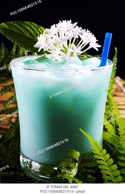 A tropical drink garnished with flowers