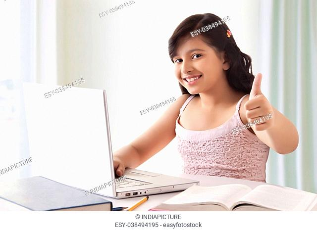 Portrait of smiling cute girl using laptop and showing thumbs up