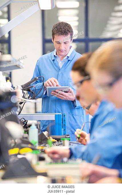 Supervisor with digital tablet at production line in circuit board manufacturing plant