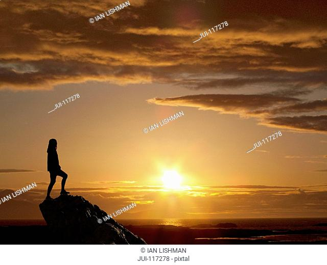 Silhouette Of Woman Standing On Mountain Peak At Sunset