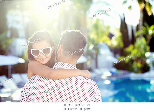 Father carrying daughter wearing heart shaped sunglasses by swimming pool