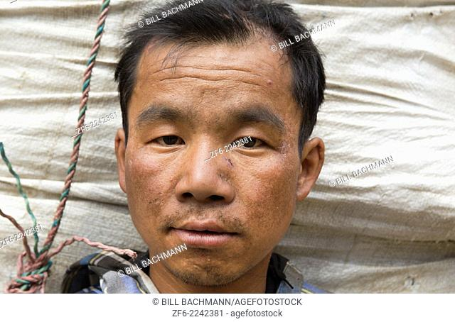 Nepal Porter poses for camera with head against basket load in Thamo, Solukhumburemote, Mt Everest, Himalayas 81