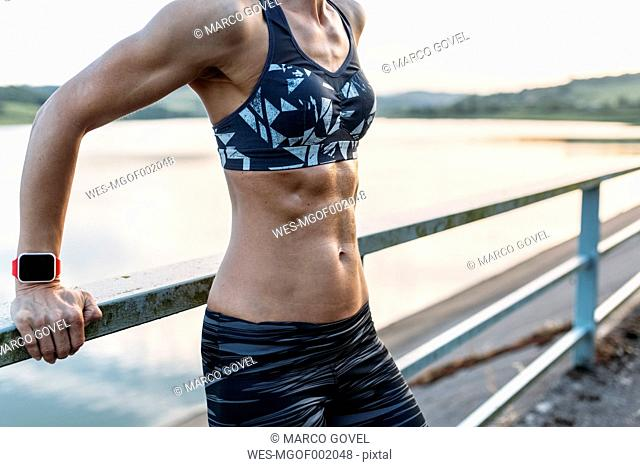Woman leaning on railing showing abdominal muscles