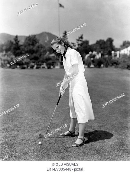 Woman playing golf on a golf course All persons depicted are not longer living and no estate exists Supplier warranties that there will be no model release...