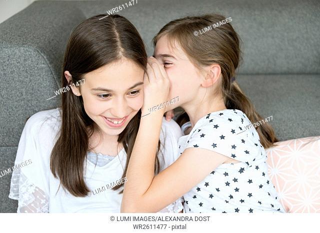 Girl whispering to girlfriend