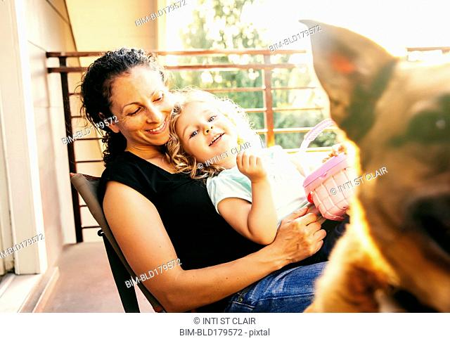 Caucasian mother and daughter playing with dog on patio