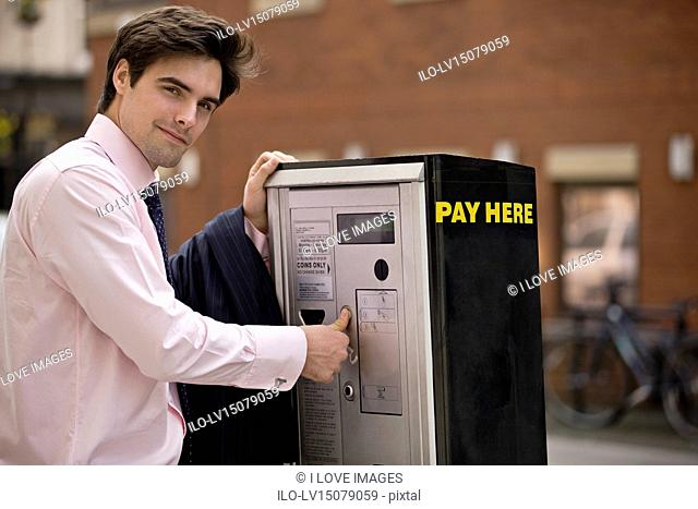 A businessman buying a ticket from a parking meter