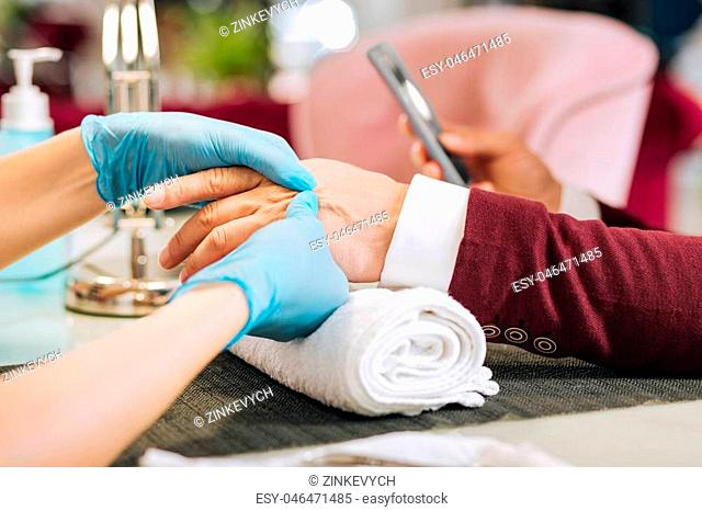 Preparation before manicure. Close up of female hands massaging male hands and wearing blue gloves