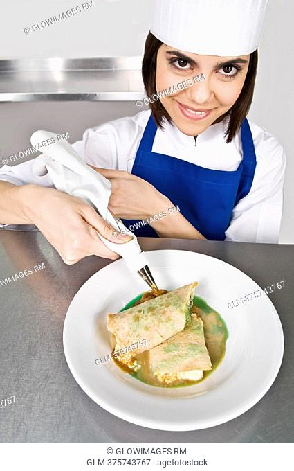 Female chef icing pastries and smiling