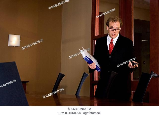 Portrait of businessman holding binder and cell phone in boardroom
