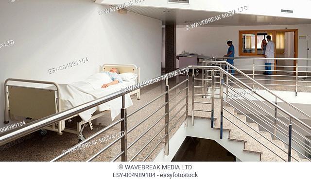 Patient lying in bed in quiet corridor in hospital