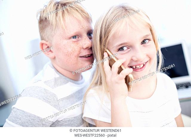 Brother and sister using cell phone together