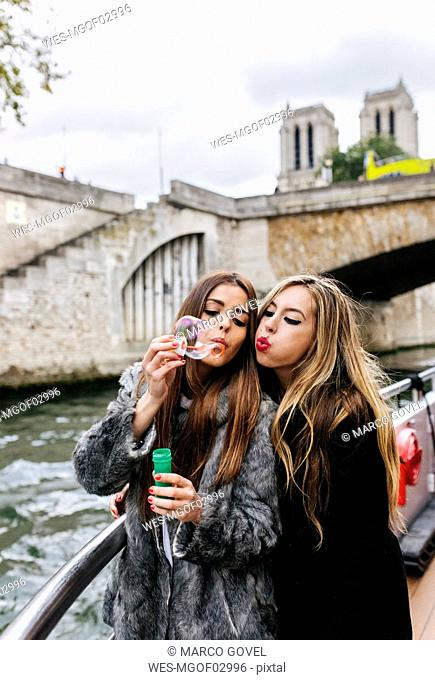 Paris, France, portrait of two friends blowing soap bubbles together