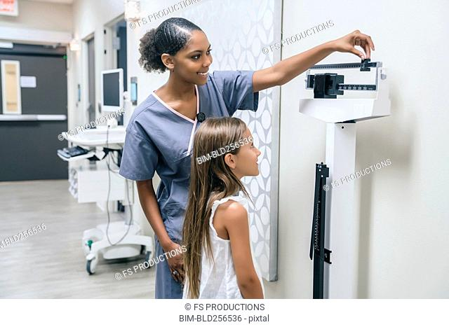 Nurse weighing girl on scale