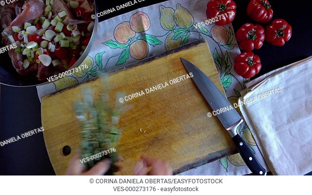 Woman adding fresh rosemary in a bowl with pork spareribs, tomatoes and spring onions
