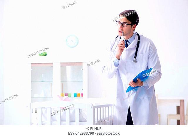 Man male pediatrician near baby bed preparing to examine
