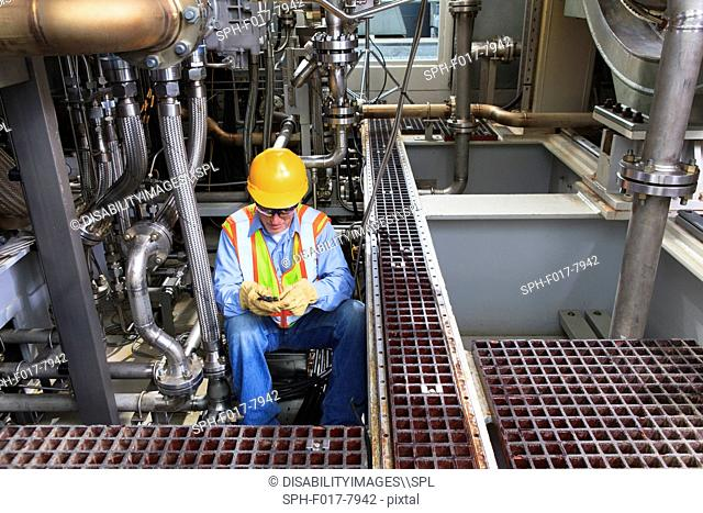 Engineer working on gas turbine which drives generators in power plant while turbine is powered down