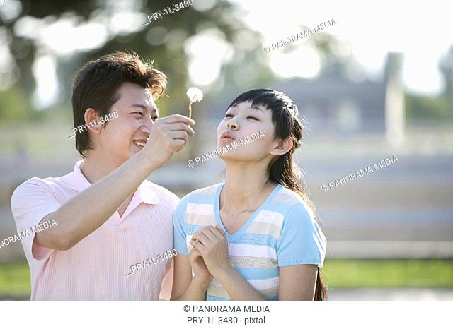 Young woman blowing dandelion flower held by man