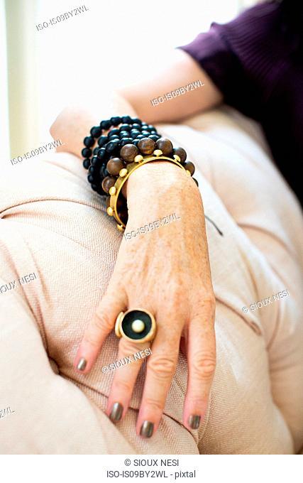 Stylish mature woman wearing bead bracelets and ring, close up of hand