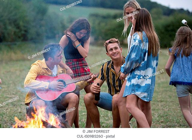 Young man playing guitar at bonfire party in park