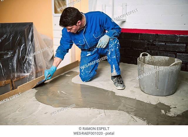 Bricklayer applying wet cement on floor