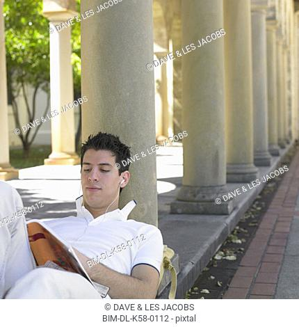 Male university student reading and listening to music, Perth, Australia