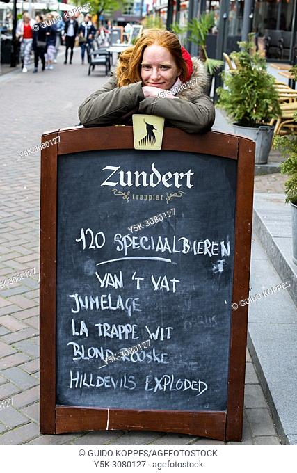 Roosendaal, Netherlands. Young, redheaded woman leanig over her favourite cafe's sidewalk billboard, before entering and having a beer with a friend