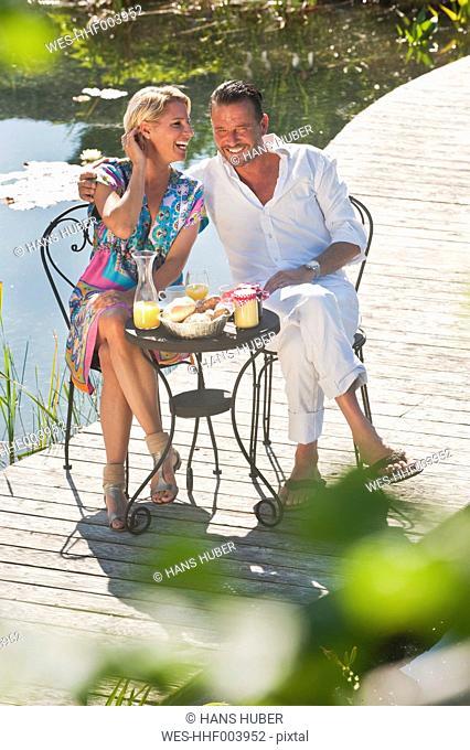 Austria, Salzburg County, Couple having breakfast on bridge over pond
