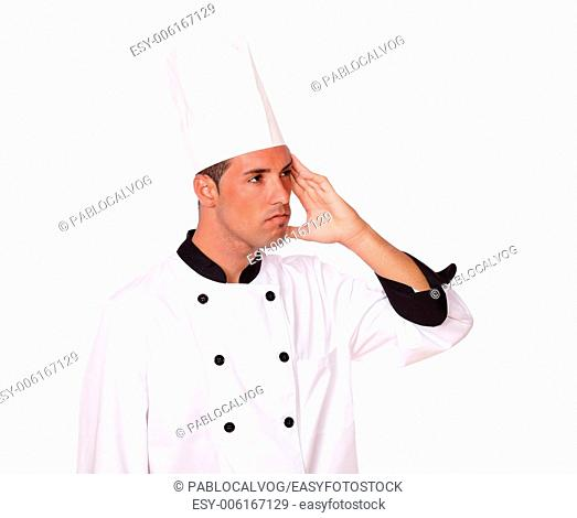 Portrait of handsome chef on white uniform with headache looking at people while standing on isolated background - copyspace
