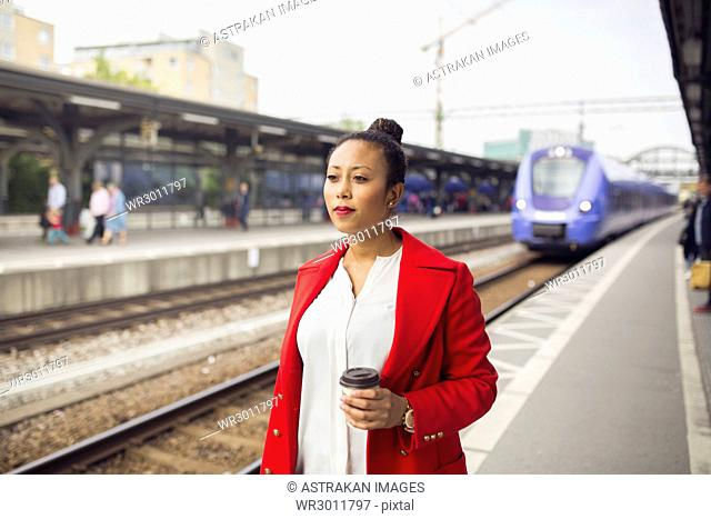 Portrait of woman in red coat waiting for train at station