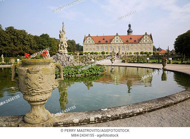 Red Geranium flowers in planter and water fountain pool with statue at the Weikersheim Palace garden in late summer, Hohenlohe region, Germany