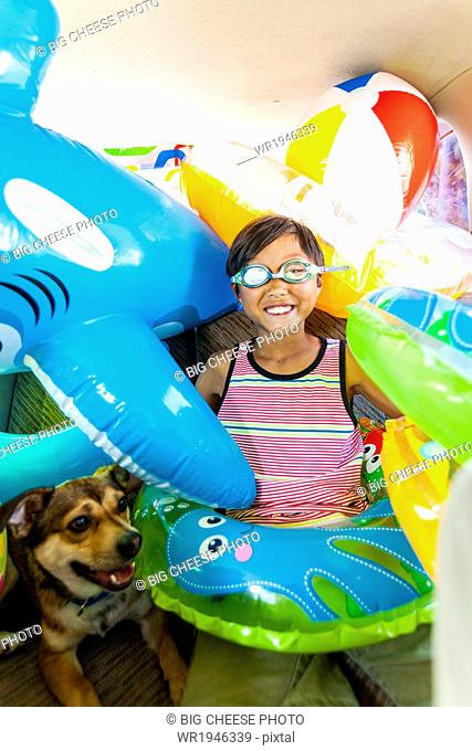 Child poses with his dog in a car full of beach toys and floaties