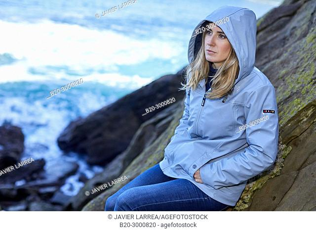 Adult woman at the coast of Santa Clara Island, Donostia, San Sebastian, Gipuzkoa, Basque Country, Spain, Europe, Raincoat, Winter