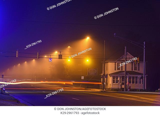 Light traffic on main street (US 2) in the fog, before dawn, Ironwood, Michigan, USA
