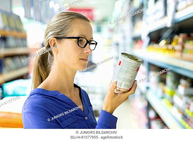 Woman studying label on wet canned food can in front of a shelf in a store. Germany