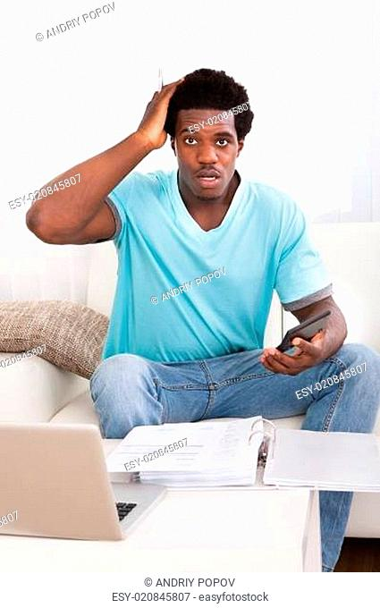 Worried Young Man Holding Calculator