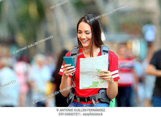Happy teenage tourist searching destination online in a smart phone walking on the street