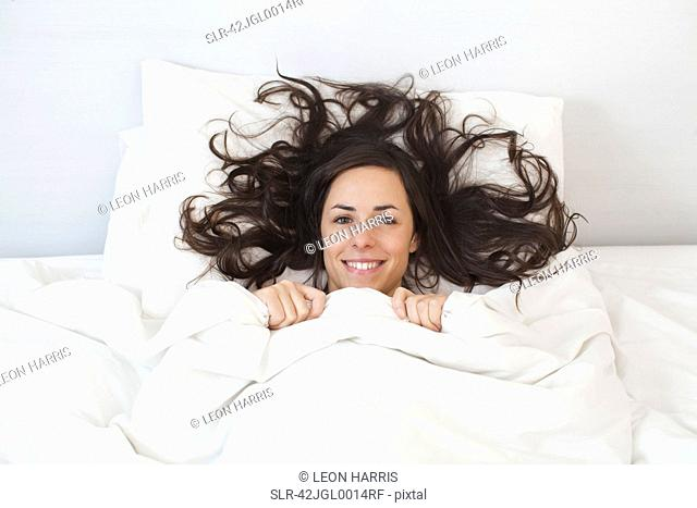 Woman laying under covers in bed
