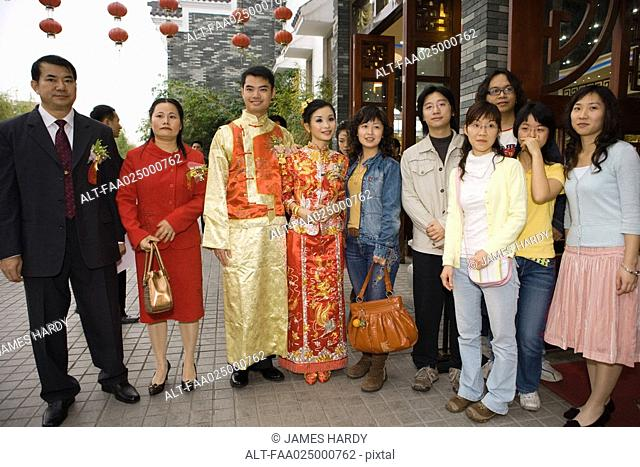 Newlyweds dressed in traditional Chinese clothing, standing with family, group portrait