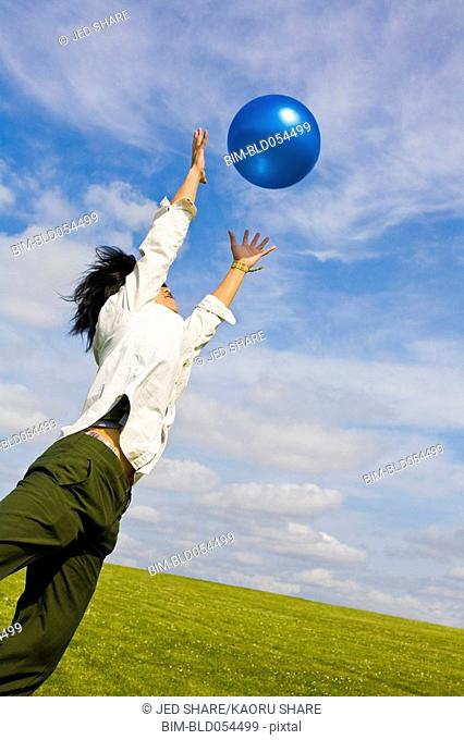 Asian woman jumping for ball
